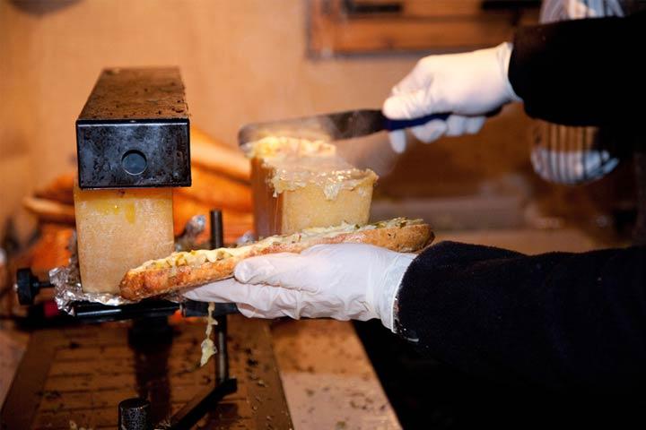 Chef beim Zubereiten eines Raclettekäsebriegel